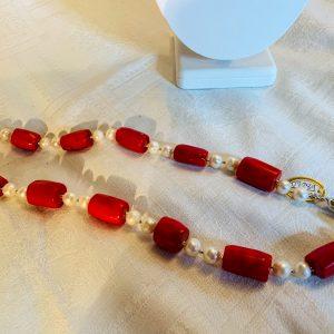 Halsband av man made röd korall